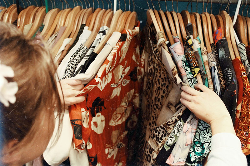Looking at various dresses hanging on wooden hangers